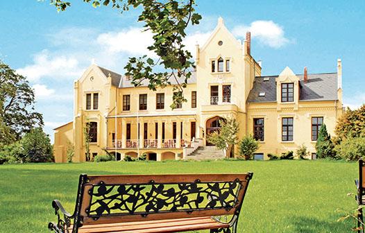 Parkbank mit Schloss Poggelow von der Seite