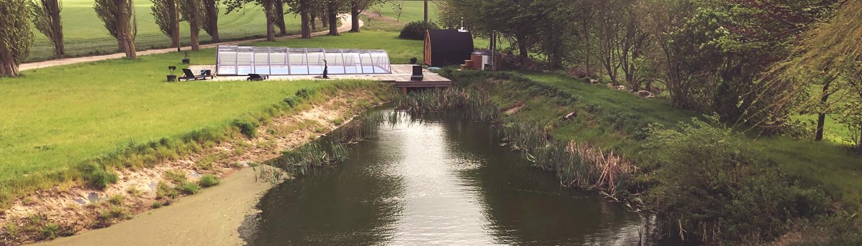 Blick vom 1.OG des Landhauses Dragun auf den großzügigen Teich sowie den überdachten Outdoor-Pool sowie die schwedische Badetonne und Sauna.